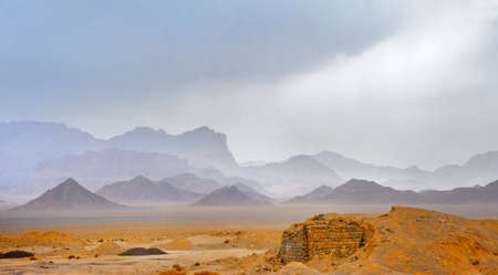 desert area in the central part of Iran, on a background towers a mountain chain, in the sky rain clouds Imagens - 77342362