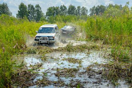 Offroad-Wettbewerbe, zwei SUVs überwinden ein Wasserhindernis, eine Reihe von Spritzern Standard-Bild - 77361664