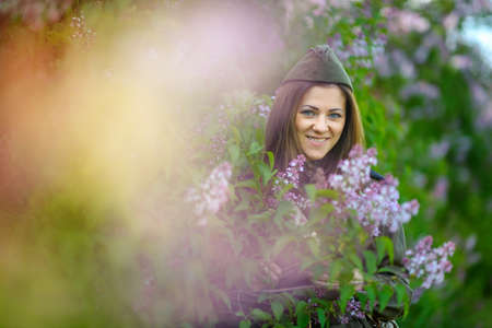 girl in a military uniform in the spring park, near the big blossoming lilac bush