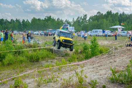 truck driver: Belarus, Brest, 2016 - off-road competitions, brightly yellow SUV in a jump overcomes an obstacle