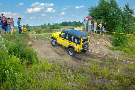 Belarus, Brest, 2016 - off-road competitions, brightly yellow SUV overcomes an obstacle
