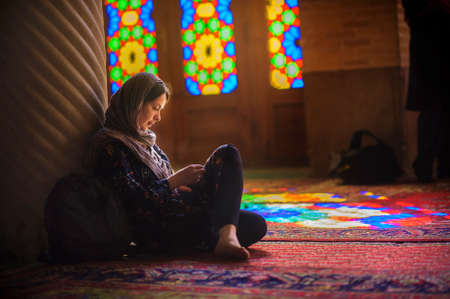 young girl in a scarf sits on a floor in the mosque, is attentive that that reads, bright multi-colored patches of light Foto de archivo