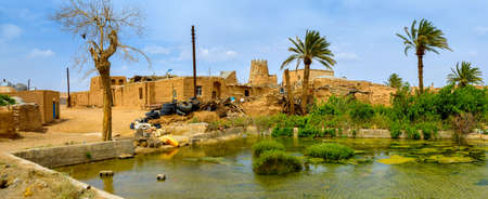 The old pise-walled Iranian village located in a desert part of the country, in the center of the village the big tank for collecting water