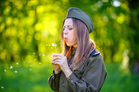 woman the military in the beautiful spring park at sunset with a dandelion in hands