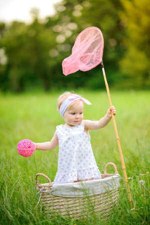 net: girl plays with a net in the park, standing in a basket tries to catch an insect Stock Photo