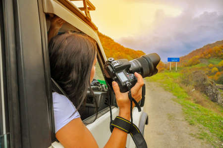 photographer looks out with the camera of the moving car, in search of a good shot Stock Photo - 89879673