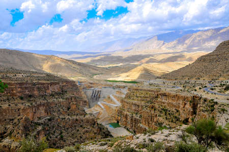 road in the hilly terrain of Iran runs along a big kanyen, the dam nearby settles down