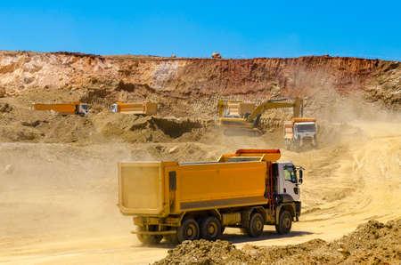 ensemble de camions et l'excavatrice travaillent en carrière à l'exploitation minière