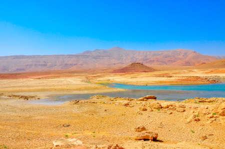 彼女の下部で、乾燥まで湖の小さな山の尾根の地平線上の明るい晴れた日にモロッコの中央の砂漠部分のパノラマ