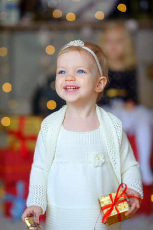 little girl with beautiful blue eyes, with a gift in hands, cheerfully smiles