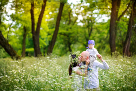 family walks in the beautiful park on a sunset, play and have fun, the father carries the kid on shoulders