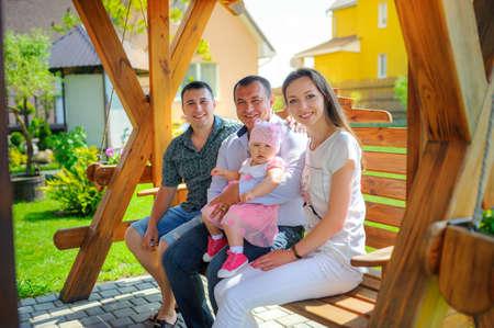 幸せな家族、彼の腕は、すべて彼の家の近くのブランコに座って彼の孫娘を保持の祖父 写真素材