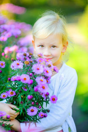 beautiful girl is walking in the evening park, hugging a big bouquet of flowers