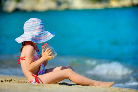een klein meisje in een grote strandhoed rust op het strand, drinkend vers vruchtensap Stockfoto