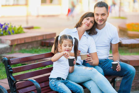 happy family kidding in the city, sitting on a bench and eating ice cream