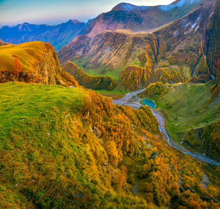 a panorama of a mountain gorge at sunset, beautiful autumn forests, a small lake at the bottom of the gorge Stock Photo