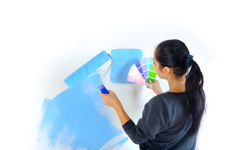room design, the girl is engaged in a choice of paints for the walls of the room, isolated on a white background  Фото со стока