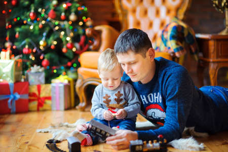 dad lying on the floor playing with his beloved son, near festive Christmas trees and boxes with gifts  Stock Photo
