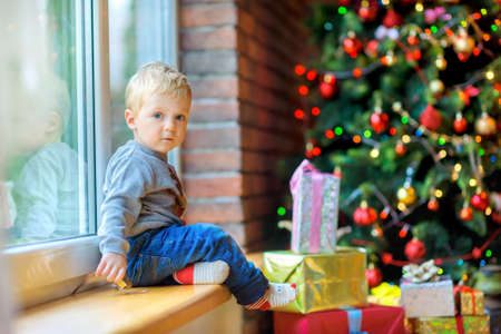 the beautiful kid sits and plays near a window, near a festive Christmas tree and set of gifts