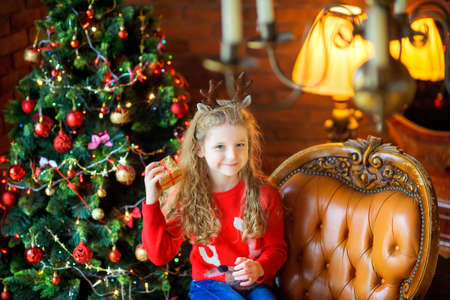 beautiful girl with a small gift sits in a chair near a festive Christmas tree