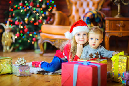 sister gently hugs her little brother sitting on the floor near the gifts