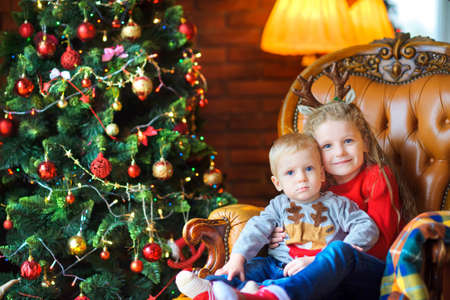 sister gently hugs her little brother sitting in a chair near a festive Christmas tree  Standard-Bild