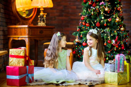beautiful little girls are sitting on the floor in the room and giving each other presents, in the background a festive Christmas tree