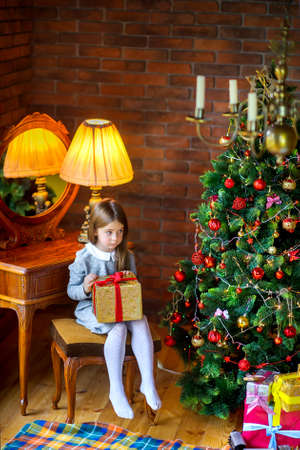 girl with a gift sits near a festive Christmas tree, looks at gifts lying under a Christmas tree