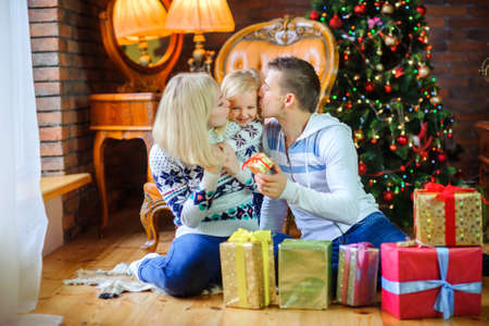 happy family sitting on the floor near the Christmas tree, giving each other presents and having fun  Standard-Bild