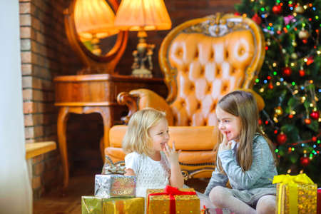 two beautiful girls play with sitting on the floor with gifts, festive Christmas tree in the background