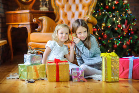 beautiful sisters sit on the floor near the Christmas tree and take gifts  Standard-Bild