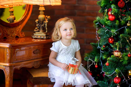 beautiful little girl near festive christmas tree holding gift in hands and smiling