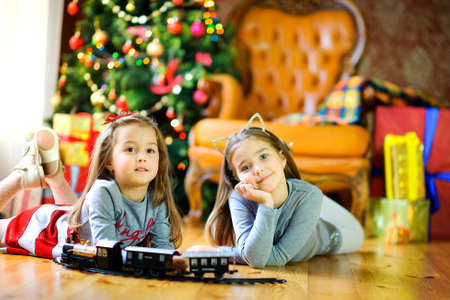 Christmas morning, two sisters playing with gifts lying on the floor, on the background of a festive Christmas tree