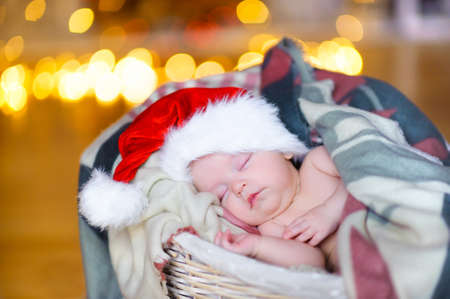 beautiful baby in a Santa Claus hat sipping lying in a basket, against a background of bright festive garlands