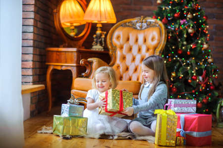 beautiful sisters sit on the floor near the tree and give each other presents and have fun