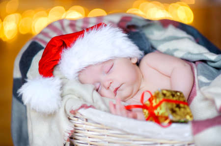 beautiful toddler in a Santa Claus hat holds a gift hand and sleeps in a basket lying in the background, bright festive lights in the background