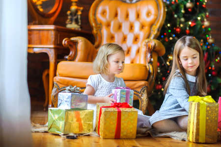 Christmas morning, two sisters open gifts sitting on the floor near a festive Christmas tree
