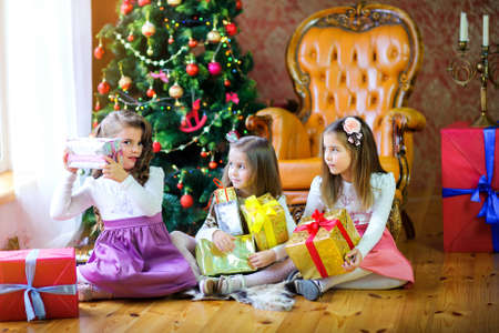 Christmas morning, three sisters on the floor near the Christmas tree with gifts in hands