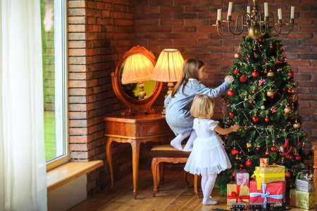 preparing for the holiday, two beautiful sisters decorate the Christmas tree with balls