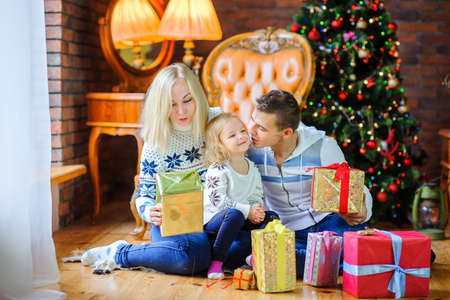 Christmas morning, a big happy family gives each other presents, sitting near the Christmas tree  Standard-Bild