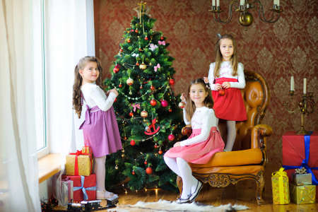 Three sisters decorate the Christmas tree with balls  Standard-Bild