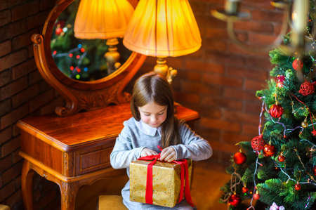 Christmas morning, beautiful little girl opens a gift sitting near the Christmas tree