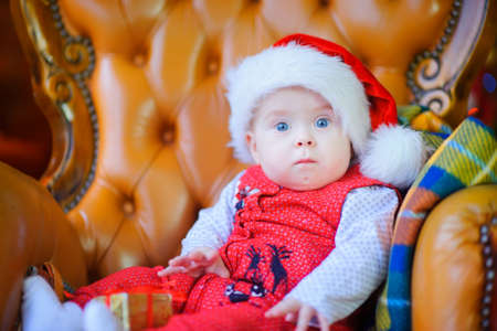 A beautiful kid in a Santa Claus hat sits on a chair and looks surprised at the camera