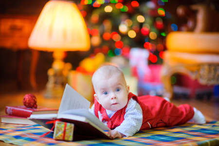 Funny kid lies on the floor near the Christmas tree and reads Christmas tales