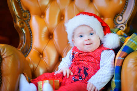 Beautiful toddler in Santa Claus cap sits on chair smiling and looks at camera Stock Photo