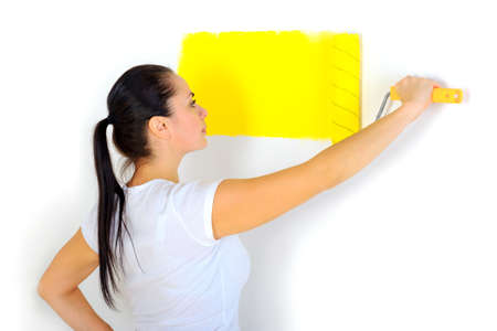 repair in the house, the girl paints a roller of a wall in yellow color Standard-Bild
