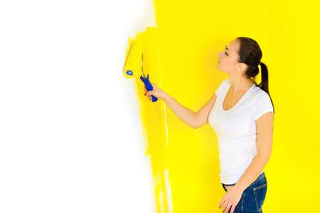 girl paints a roller against a wall in a room, repairs in the house