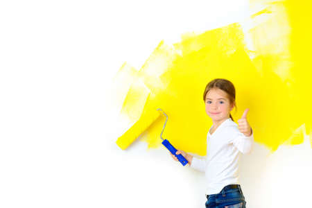 Beautiful girl paints a roller with a wall in the room, smiling and shows class Standard-Bild