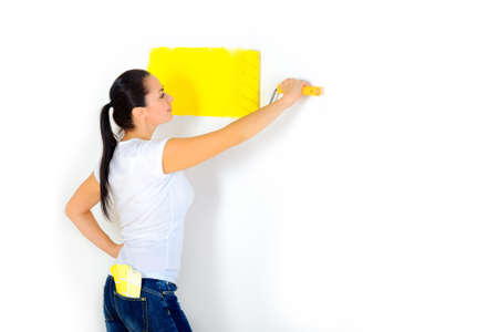the girl began to paint the walls with a roller in a rich yellow color, repairing the house Standard-Bild