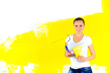 Painter holds a roller in his hands and chooses a color for painting the walls.